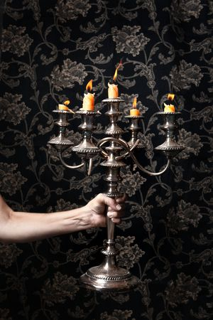 burned out: A candelabra is held by an outstretched arm. The candles are almost burned out.