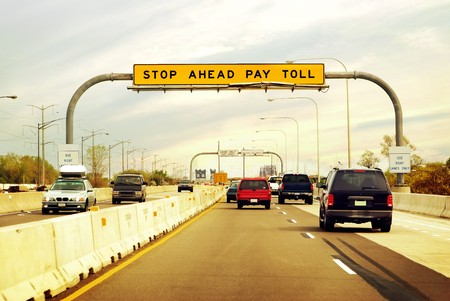 fare: Cars on the highway leading in and out of a toll booth Stock Photo