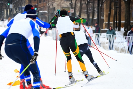 skiers: nordic skiers race around a  corner on a downtown street