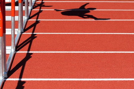shadow of a person jumping over a hurdle on a red track Banque d'images