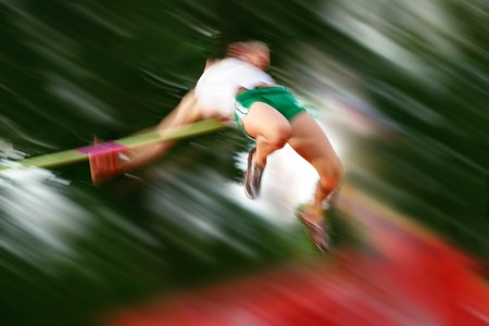 sports bar: Motion blur of a high jumper going over the bar