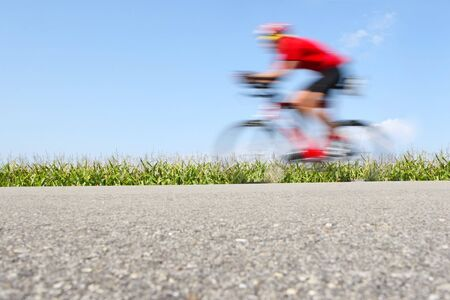 A bicyclist speeds by on a country road
