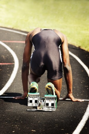 a runner is in the starting blocks posed to start a race Reklamní fotografie