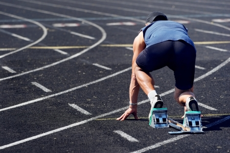 A man is about to sprint off of the starting line