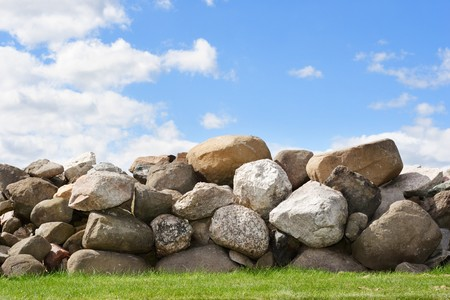 stone wall: A stone wall with a bright blue sky with white puffy clouds Stock Photo