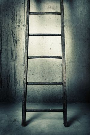 an old wooden ladder is leaning up against a concrete wall