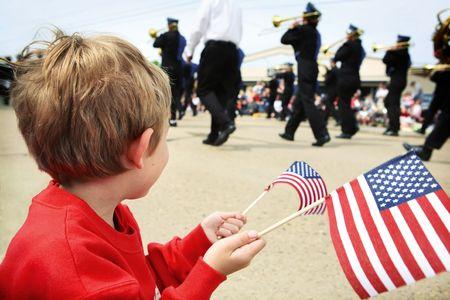 een jonge jongen kijkt een parade terwijl zwaaien een paar van de Amerikaanse Vlaggen