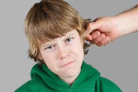 pulling faces: a teenaged boy is being punished by his father Stock Photo