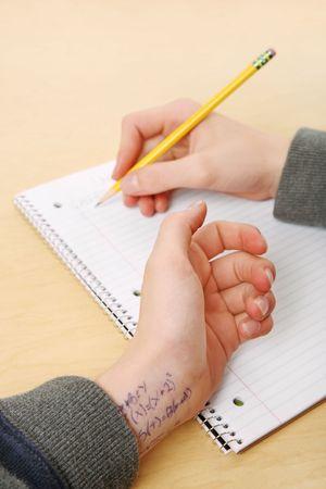 eine enge bis Händen eines Jugendlichen, der die Antworten auf seine Prüfung auf seine Arme Standard-Bild