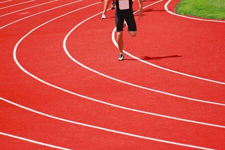 a close up of a corner of a  red track with runners