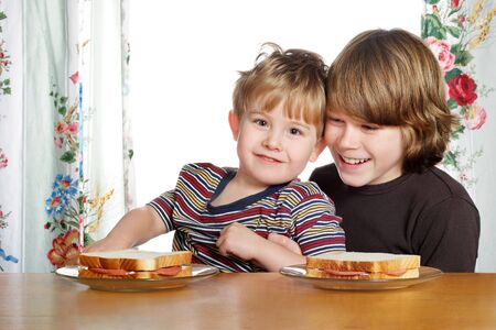 a teenage boy and his younger brother are eating lunch photo