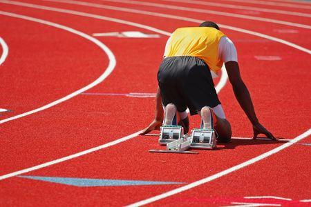 un corredor en una pista roja en el punto de partida Foto de archivo