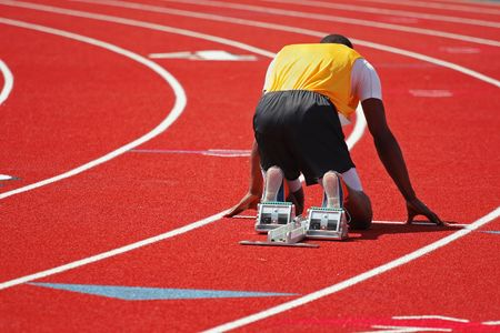 a runner on a red track in the starting block