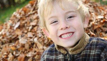 a young boy smiles at the camera while standing in front of a pile of leaves