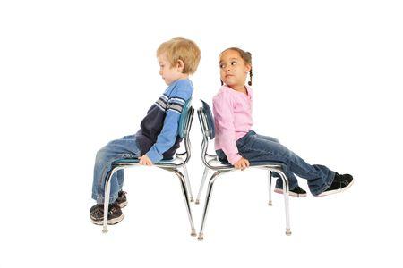 twee kinderen zitten op stoelen die rug aan rug
