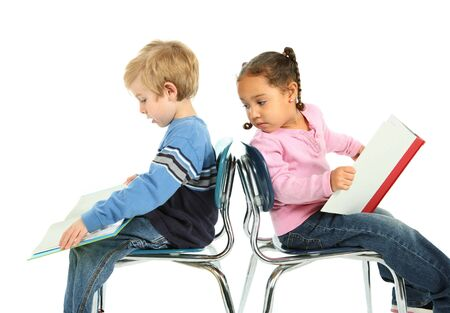 two children are reading books while sitting in  school chairs
