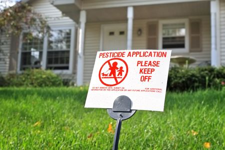 A close up of a pesticide sign with a house in the background