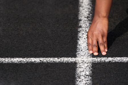 a close up of a hand on the starting line of a track