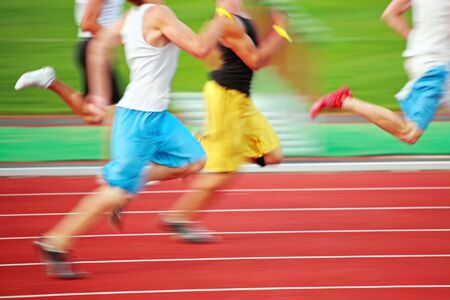 a close up of a group of runners on a red track Banque d'images
