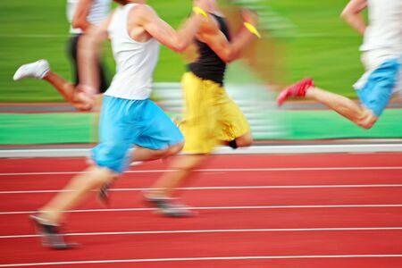 un primer plano de un grupo de corredores en una pista roja