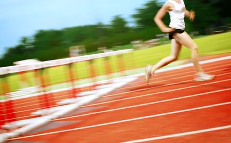 a motion blur of a runner that has just cleared a hurdle