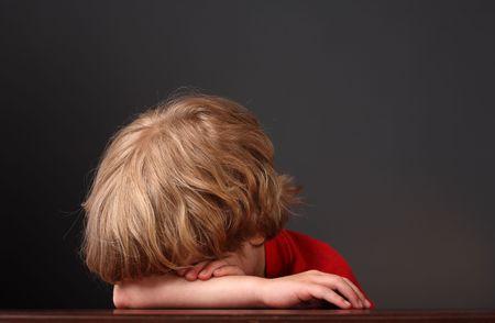 若い男の子は彼の腕彼の机で眠っている彼として彼の頭を置く