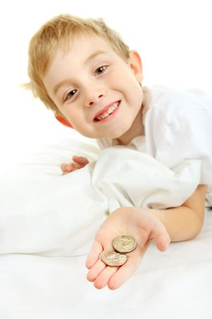 a young boy holds out two quarters that he found under his pillow that he got from the tooth fairy for loosing a  tooth.