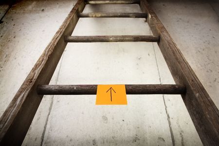a ladder with a sticky note that has a arrow drawn on it that is pointing up. Reklamní fotografie