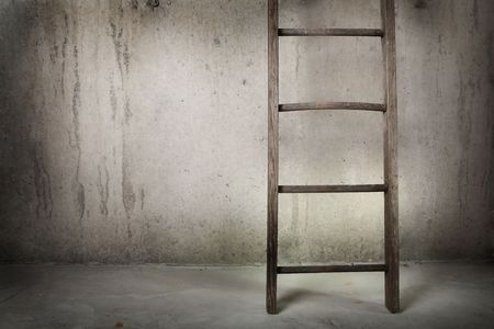 délivrance: une vieille échelle en bois est appuyé contre un mur de béton