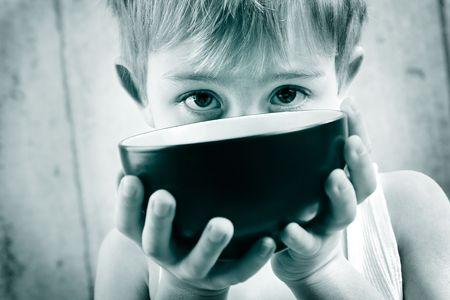 een jonge jongen in monotone peeks over een lege pot rijst