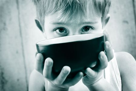 a young boy in monotone peeks over an empty rice bowl Banque d'images