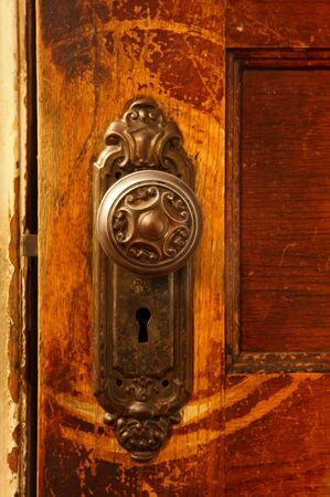 a close up of a vintage door knob on a wooden door