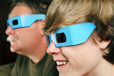 a father and son are watching a 3D movie while wearing 3D glasses photo