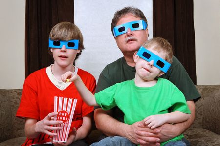 a father and his two sons are watching a 3D movie while wearing 3D glasses photo