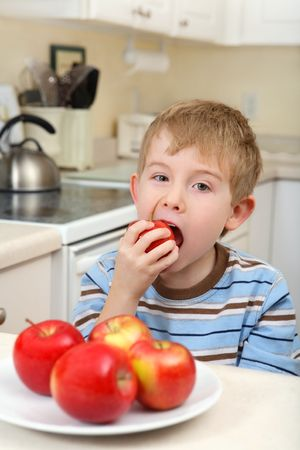 a young boy sits in the kitchen eating an apple Reklamní fotografie