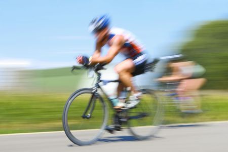 motion blurred bicyclists race through the countryside