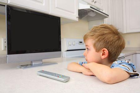 若い男の子のフラット スクリーン テレビ台所に座っている時計します。画面が空白、画面に画像が自分がデザイナーに追加できるようにします。