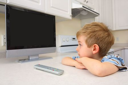 a young boy watches a flat screened TV while sitting in the kitchen. The screen is blank, so that the designer can add there own images to the screen.