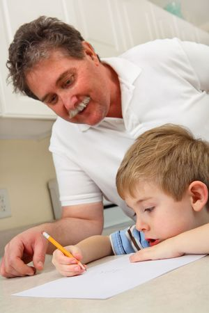 A father helps his young son who is practicing writing. Reklamní fotografie