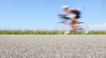 a motion blurred bicyclist races through the countryside