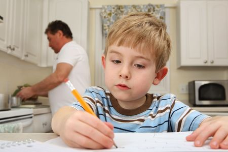 A young boy is writing while his father is cooking.