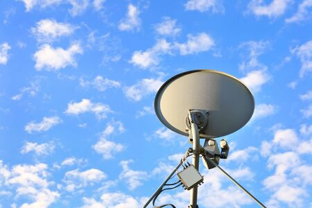 a satellite dish with a blue sky with many small cumulus clouds Reklamní fotografie
