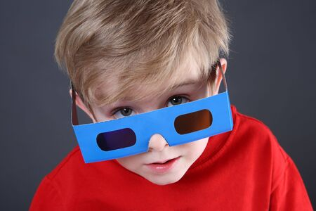 a young boy is peeking over a pair of 3D glasses
