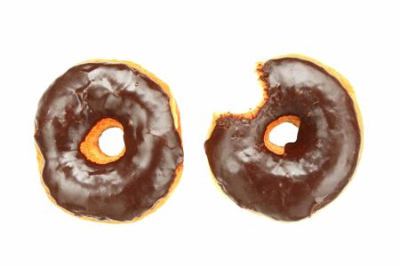 two chocolate donuts one has a bite taken out of it.