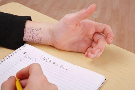 사람이 책상에 앉아 시험을 치고 있으며 손목에 답이 쓰여있다.