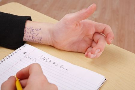 a person is at a desk taking a test and they have the answers written on their wrist