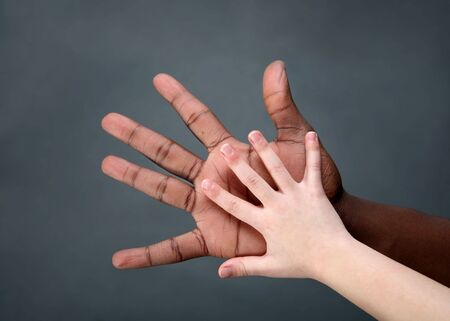 a multi-cultural image of aa young boy compares his hand to that of an adult photo