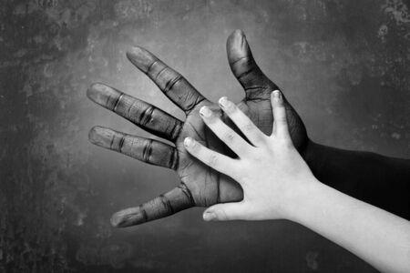 ein multikulturellen Bild der aa junge vergleicht seine Hand mit der Erwachsenen