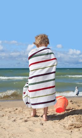 young boy on the beach wrapped in a towel