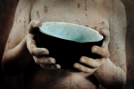 a grunge image of a young boy as he holds out an empty bowl  Archivio Fotografico
